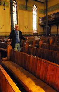 Pastor Todd stands by Edna and Vivian's Pew